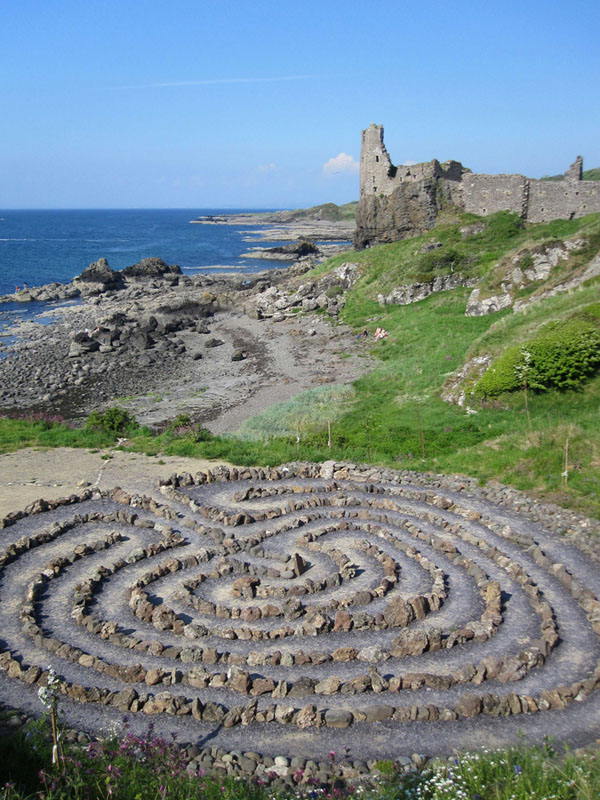 the Dunure Castle Labyrinth positioned in the foreground with the castle itself atop a hill on the coast beyond.