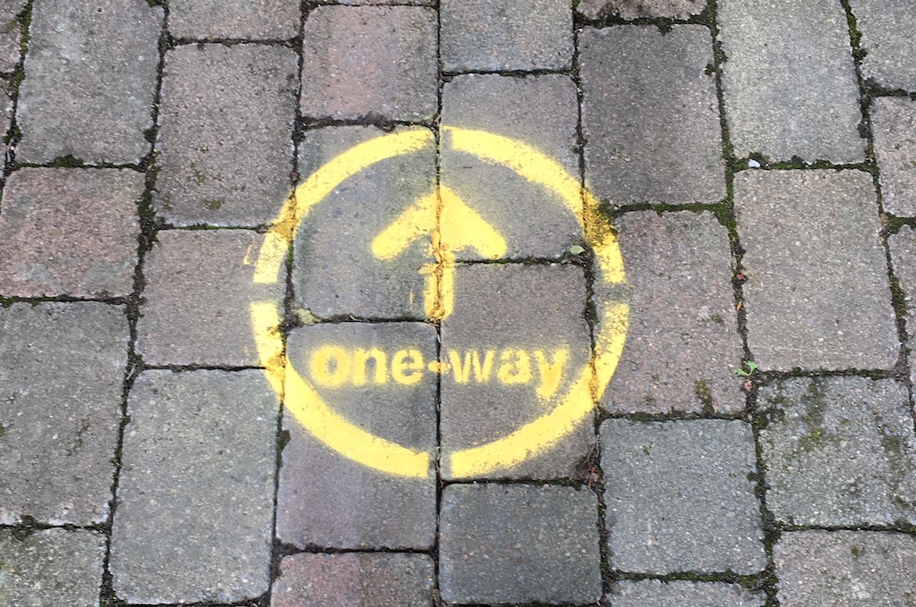 One way sign spray painted onto the ground